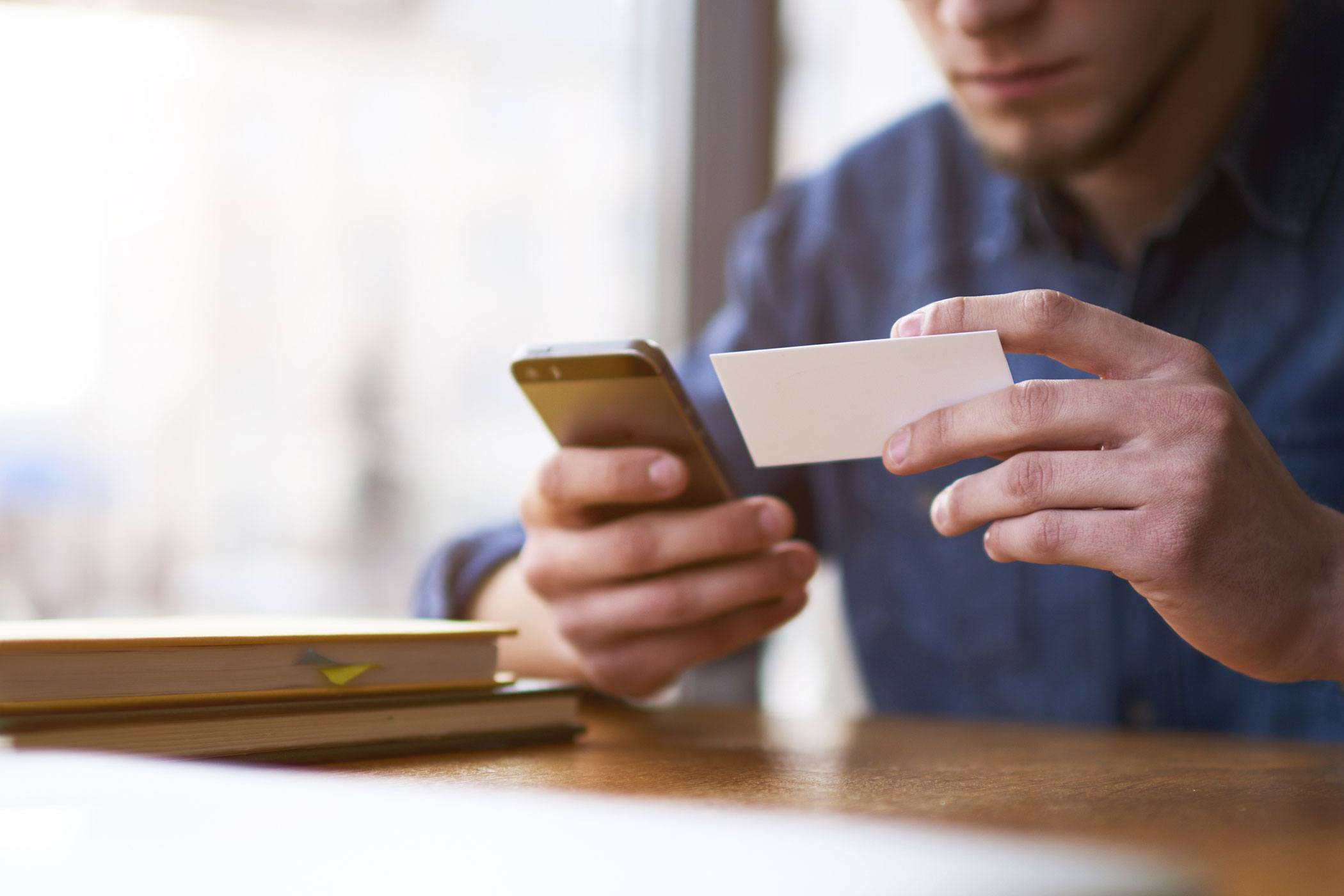 man holding business card in left hand and smart phone in his right hand at desk