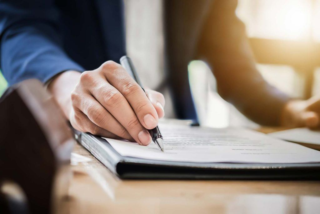 a man's hand holding a pen and signing a contract